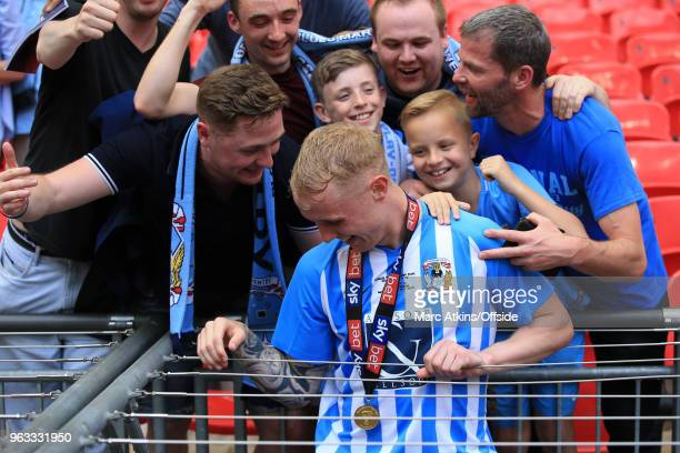 Jack Grimmer of Coventry City appears to get stuck between metal wires after celebrating with the fans during the Sky Bet League Two Play Off Final...