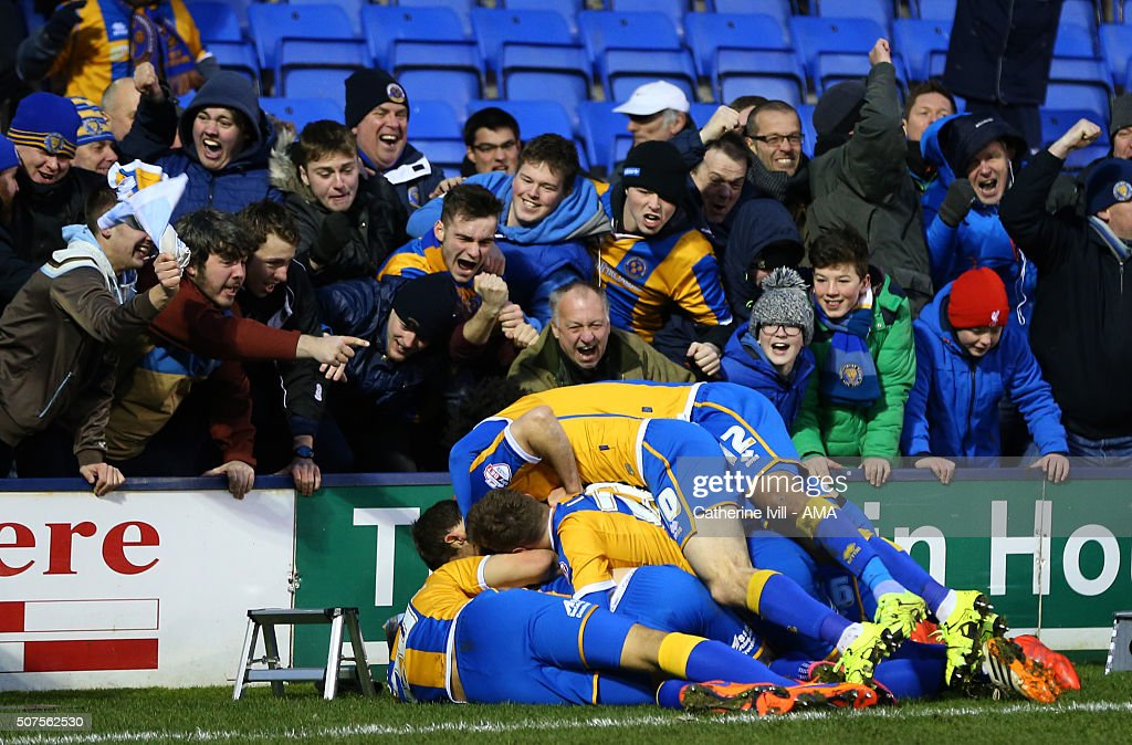 Jack Grimmer of Shrewsbury Town is mobbed by his team mates and fans after he scores to make it 3-2 during the Emirates FA Cup match between Shrewsbury Town and Sheffield Wednesday at New Meadow on January 30, 2016 in Shrewsbury, England.