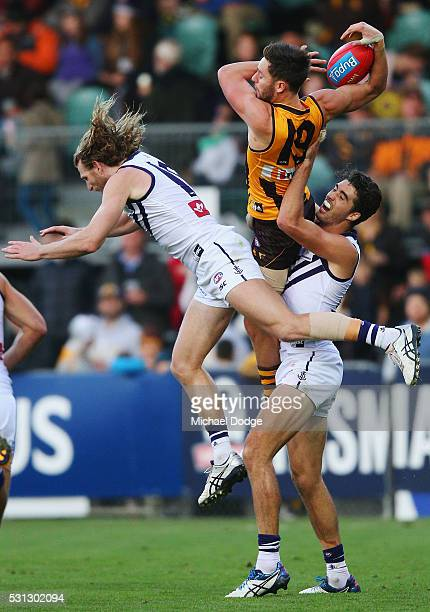Jack Gunston of the Hawks competes for the ball over David Mundy of the Dockers during the round eight AFL match between the Hawthorn Hawks and the...