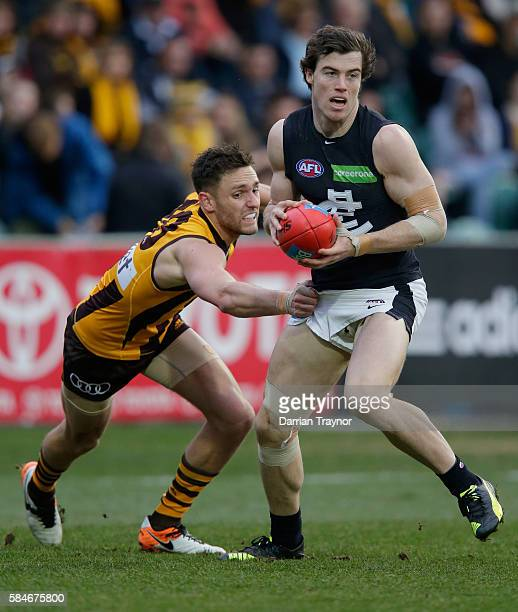 Jack Gunston of the Hawks tackles Lachie Plowman of the Blues during the round 19 AFL match between the Hawthorn Hawks and the Carlton Blues at...