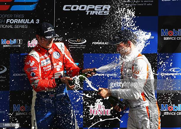 Jack Harvey of Great Britain and driver of the Carlin Dallara F312 Volkswagen sprays champagne over Harry Tincknell after winning the Cooper Tires...