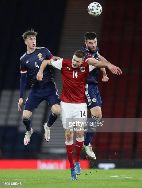 Jack Hendry and Grant Hanley of Scotland compete for a header with Sasa Kalajdzic of Austria during the FIFA World Cup 2022 Qatar qualifying match...