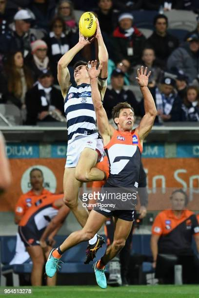 Jack Henry of the Cats marks over Matt De Boer of the Giants during the round seven AFL match between the Geelong Cats and the Greater Western Sydney...