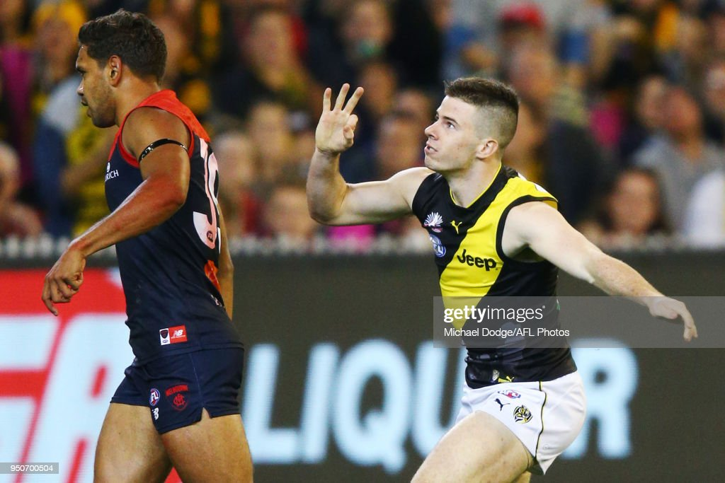 Jack Higgins of the Tigers celebrates a goal next to Neville Jetta of the Demons during the 2018 AFL round five match between the Melbourne Demons and the Richmond Tigers at the Melbourne Cricket Ground at Melbourne Cricket Ground on April 24, 2018 in Melbourne, Australia.