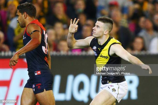 Jack Higgins of the Tigers celebrates a goal next to Neville Jetta of the Demons during the 2018 AFL round five match between the Melbourne Demons...