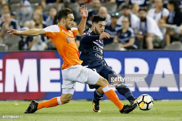 Jack Hingert of the Roar and Christian Theoharous of the Victory compete during the round six ALeague match between the Melbourne Victory and...
