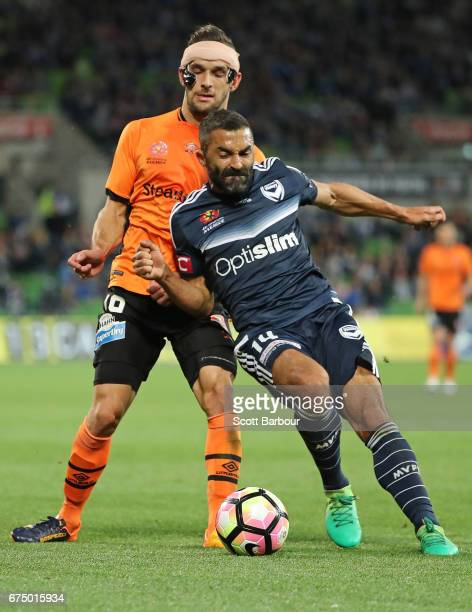Jack Hingert of the Roar and Fahid Ben Khalfallah of the Victory compete for the ball during the ALeague Semi Final match between Melbourne Victory...