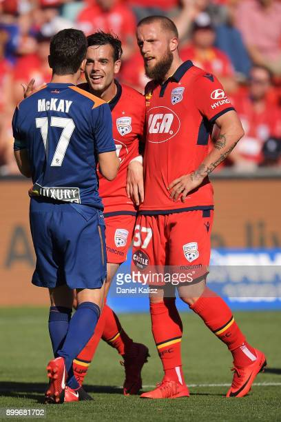 Jack Hingert of the Roar reacts to Nikola Mileusnic and Daniel Adlung of United during the round 13 ALeague match between Adelaide United and...