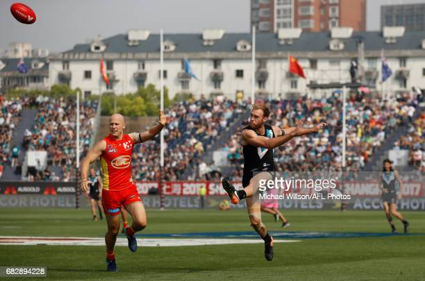 Jack Hombsch of the Power kicks the ball clear of Gary Ablett of the Suns during the 2017 AFL round 08 match between the Gold Coast Suns and Port...