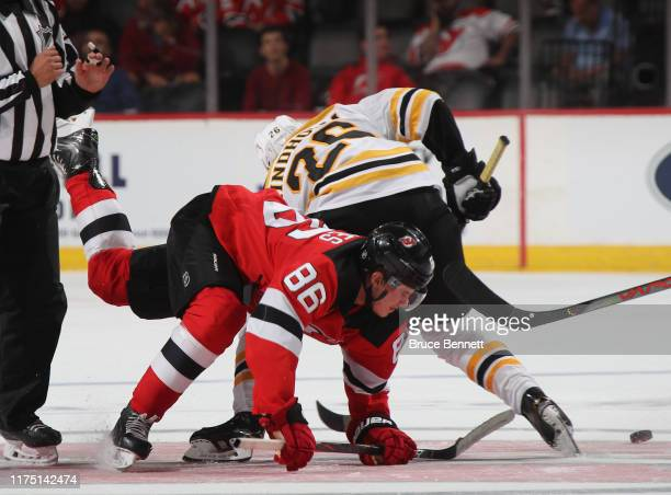 Jack Hughes of the New Jersey Devils and Par Lindholm of the Boston Bruins battle on the faceoff during the third period during preseason action at...