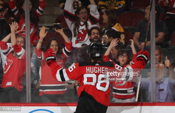 Jack Hughes of the New Jersey Devils celebrates his game winning goal at 41 seconds of overtime against the Boston Bruins during preseason action at...