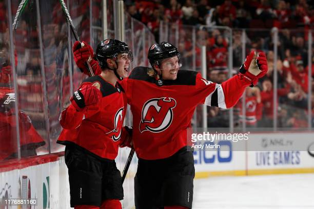 Jack Hughes of the New Jersey Devils celebrates with teammate Sami Vatanen after scoring his first career NHL goal in the first period against the...