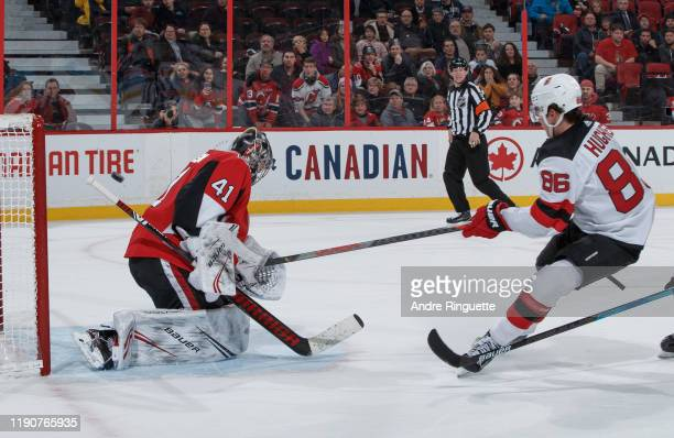 Jack Hughes of the New Jersey Devils scores the game-winning overtime goal against Craig Anderson of the Ottawa Senators at Canadian Tire Centre on...