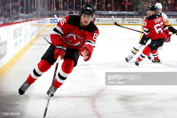 Jack Hughes of the New Jersey Devils skates with the puck against the Pittsburgh Penguins at The Prudential Center on March 18, 2021 in Newark, New...