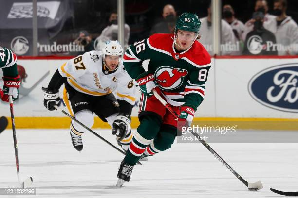 Jack Hughes of the New Jersey Devils skates with the puck against the Pittsburgh Penguins at The Prudential Center on March 20, 2021 in Newark, New...