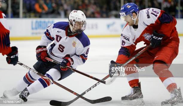 Jack Hughes of the United States skates with the puck while being chased by Martin Kaut of the Czech Republic during a quarterfinal game at the IIHF...