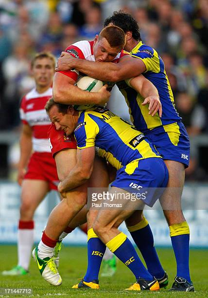 Jack Hughes of Wigan is tackled by Adrian Morley and Michael Monaghan of Warrington during the Super League match between Warrington Wolves and Wigan...