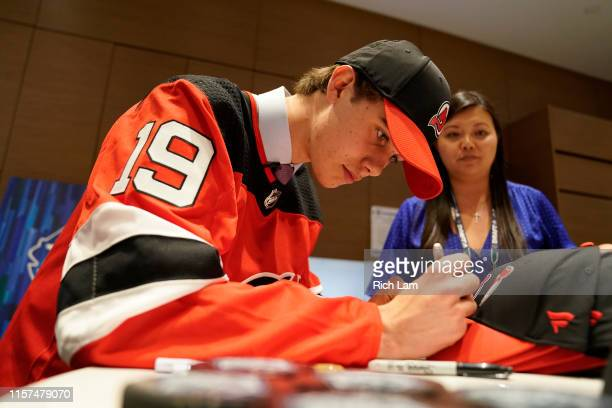 Jack Hughes signs his autograph after being selected first overall by the New Jersey Devils during the first round of the 2019 NHL Draft at Rogers...