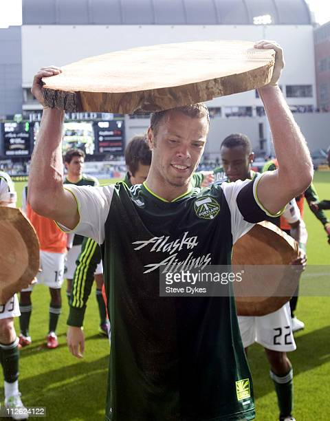 Jack Jewsbury of the Portland Timbers holds a slab of log indicating that he scored a goal celebrates in front of Timbers fans after the game at...