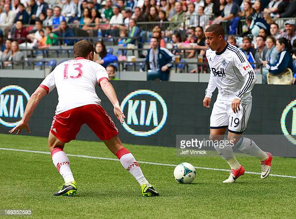 Jack Jewsbury of the Portland Timbers looks on as Erik Hurtado of the Vancouver Whitecaps FC plays the ball during their MLS game on May 18 2013 at...