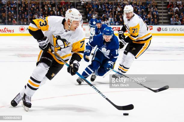 Jack Johnson and Evgeni Malkin of the Pittsburgh Penguins skates against Mitchell Marner of the Toronto Maple Leafs during the first period at the...