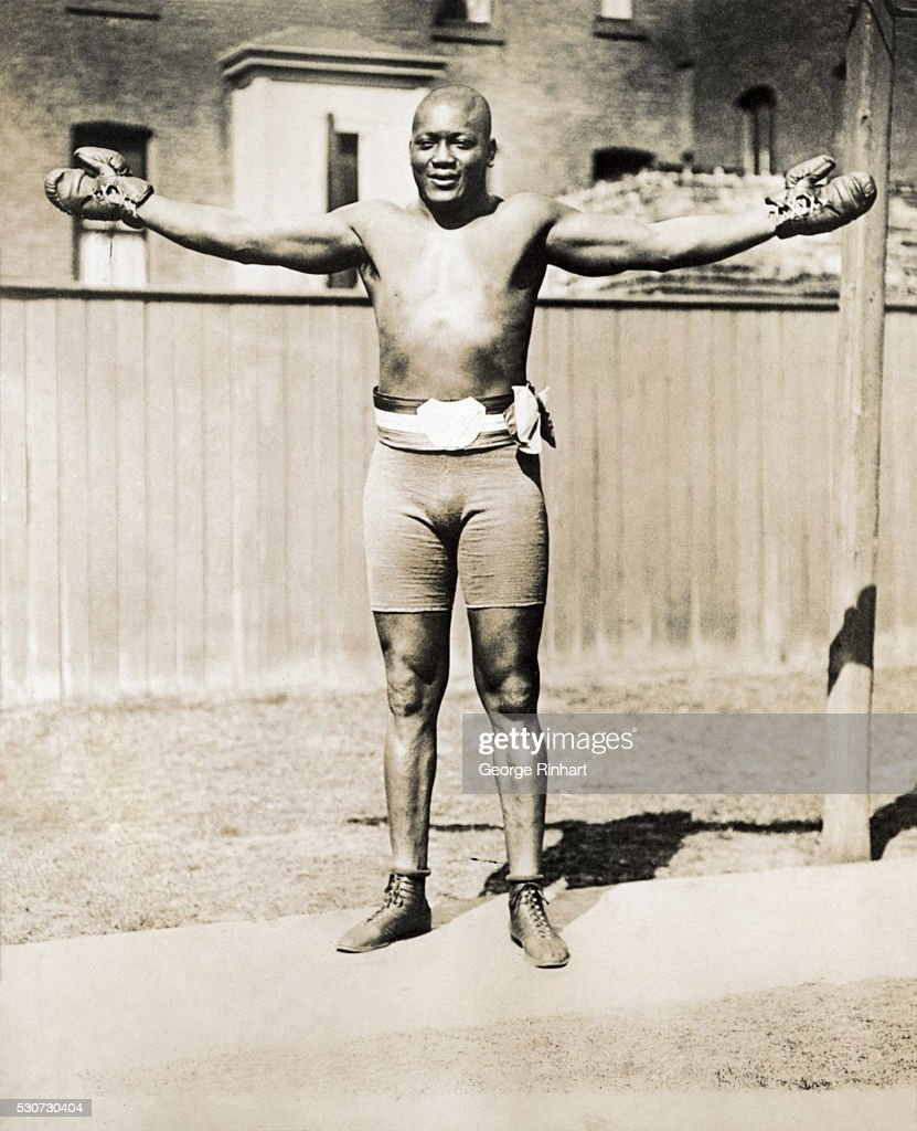 Jack Johnson is shown in his boxing trunks, arms spread. Undated full-length photograph.