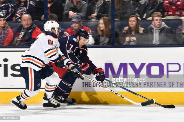 Jack Johnson of the Columbus Blue Jackets attempts to skate the puck around Yohann Auvitu of the Edmonton Oilers during the third period of a game on...