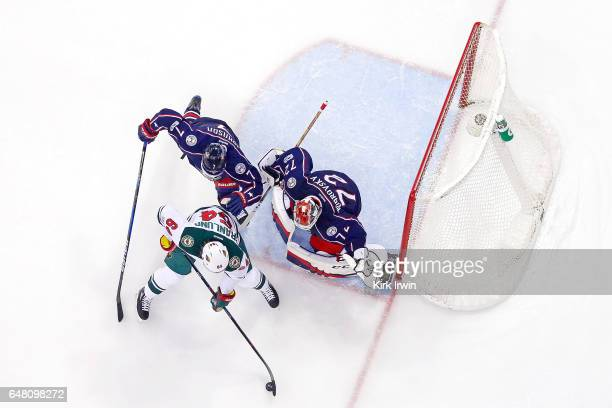 Jack Johnson of the Columbus Blue Jackets checks Mikael Granlund of the Minnesota Wild as Sergei Bobrovsky of the Columbus Blue Jackets looks to make...