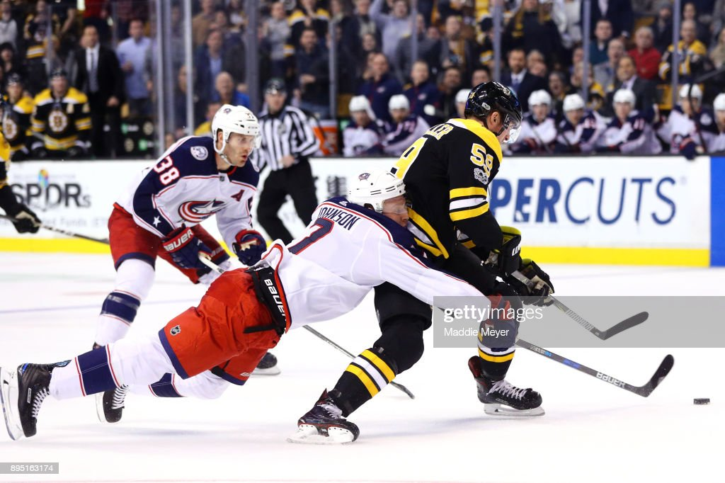 Jack Johnson #7 of the Columbus Blue Jackets is called for hooking against Tim Schaller #59 of the Boston Bruins during the third period at TD Garden on December 18, 2017 in Boston, Massachusetts. The Bruins defeat the Blued Jackets 7-2.