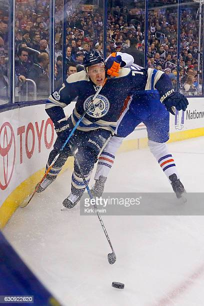 Jack Johnson of the Columbus Blue Jackets is held by Jesse Puljujarvi of the Edmonton Oilers during the first period on January 3 2017 at Nationwide...