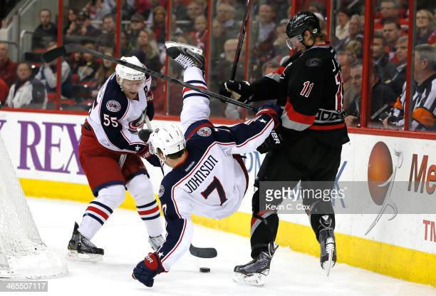 Jack Johnson of the Columbus Blue Jackets is upended while battling for the puck against Jordan Staal of the Carolina Hurricanes at PNC Arena on...