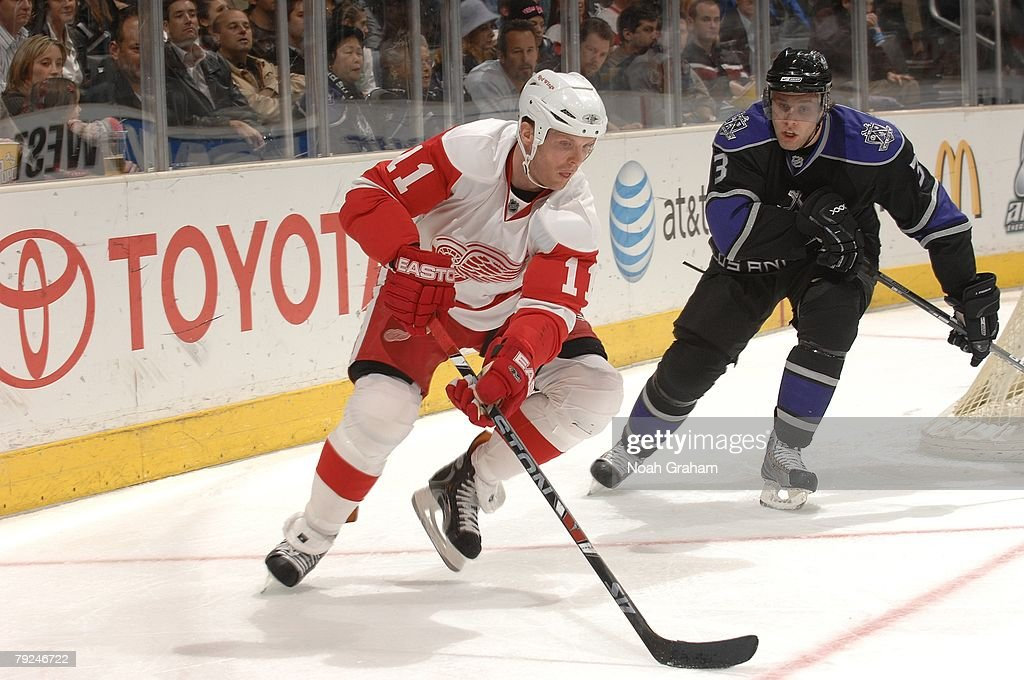 Jack Johnson #3 of the Los Angeles Kings defends alongside the boards against Dan Cleary #11 of the Detroit Red Wings on January 22, 2008 at the Staples Center in Los Angeles, California