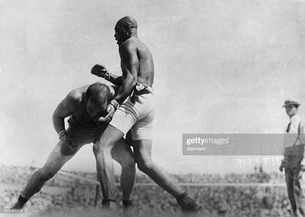 Jack Johnson, one of the cleverest defensive fighters in ring history, blocked most of Jeffries punches and Jeff landed barely a dozen blows in the entire fight. Photo shows Jeff trying his famous 'crouch' which had won him many battles.