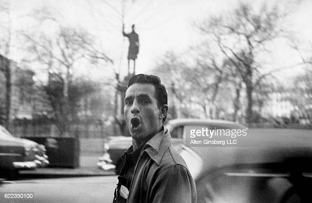 Jack Kerouac makes a funny face while walking through the Lower East Side along East 7th Street past a statue of Samuel Cox in Tompkins Square