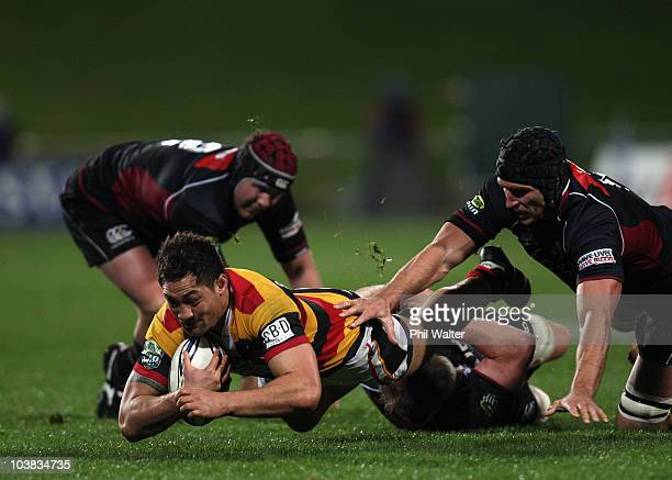 Jack Lam of Waikato breaks through the tackles of James Parsons and Anthony Boric of North Harbour during the round six ITM Cup match between North...