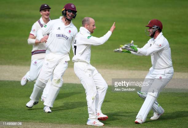 Jack Leach of Somerset celebrates the wicket of Ryan Patel of Surrey with Steve Davies Marcus Trescothick and Tom Abell of Somerset during Day Three...