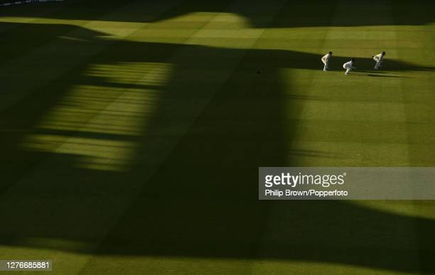 Jack Leach Steven Davies and Craig Overton of Somerset wait for a catch as the shadow from the pavilion starts to cover the field during the third...