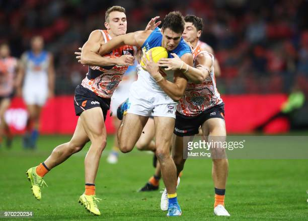 Jack Leslie of the Suns is challenged by Zac Langdon and Jonathon Patton of the Giants during the round 12 AFL match between the Greater Western...