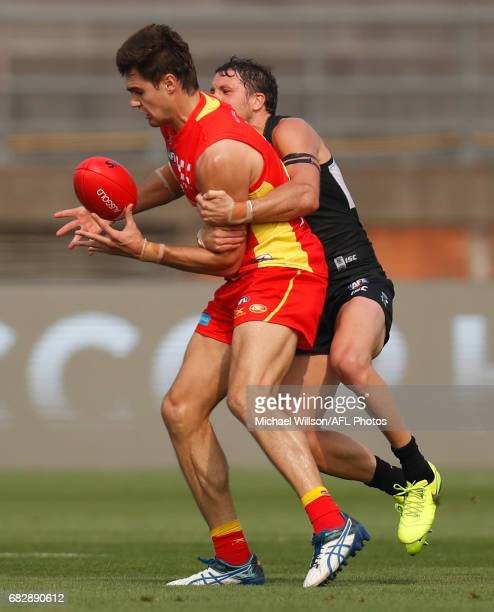 Jack Leslie of the Suns is tackled by Travis Boak of the Power during the 2017 AFL round 08 match between the Gold Coast Suns and Port Adelaide Power...