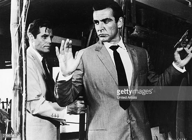 Jack Lord hold Sean Connery at gunpoint in a still from the James Bond film 'Dr No' directed by Terence Young 1962