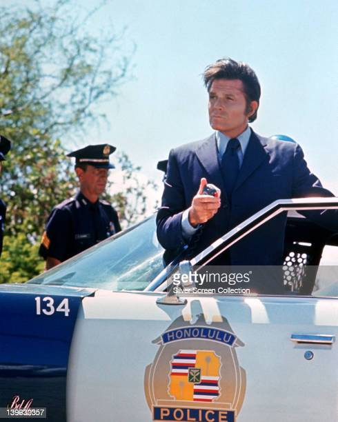 Jack Lord US actor stands in the open door of a police car in a publicity image issued for the US television series 'Hawaii Five0' USA circa 1975 The...