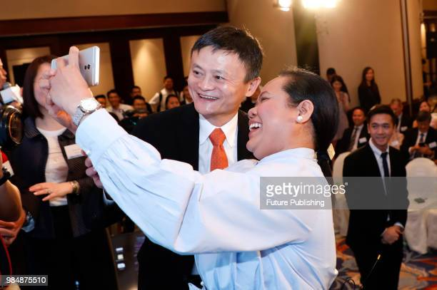 Jack Ma chairman of Alibaba Group poses for photos with a Filipino after the ceremony to launch a blockchainbase remittance solution in Hong Kong...