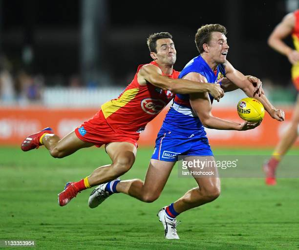 Jack Macrae of the Bulldogs is tackled by Lachie Weller of the Suns during the 2019 JLT Community Series AFL match between the Gold Coast Suns and...