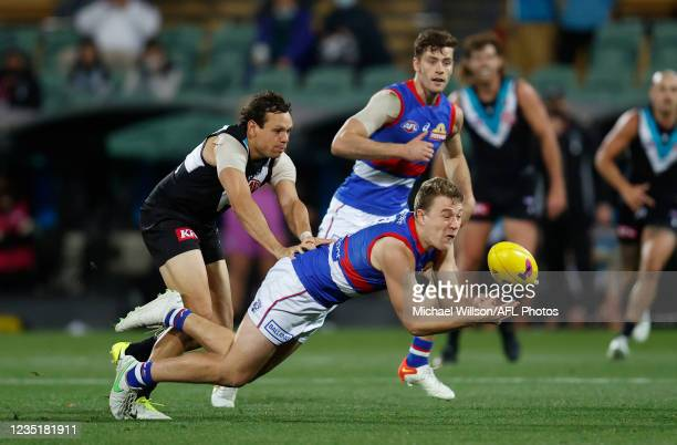 Jack Macrae of the Bulldogs is tackled by Steven Motlop of the Power during the 2021 AFL Second Preliminary Final match between the Port Adelaide...