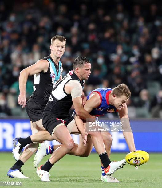 Jack Macrae of the Bulldogs under pressure form Travis Boak of the Power with Robbie Gray in the background during the 2021 AFL Second Preliminary...