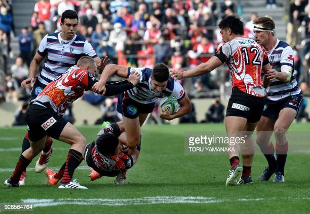 Jack Maddocks of Rebels is tackled by Ryuji Noguchi and Robbie Robinson of Sunwolves during their Super Rugby match between Japan's Sunwolves and...