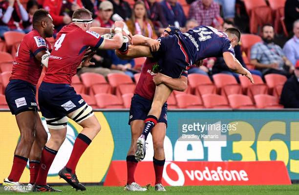 Jack Maddocks of the Rebels is picked up in the tackle by Hamish Stewart of the Reds during the round 18 Super Rugby match between the Reds and the...
