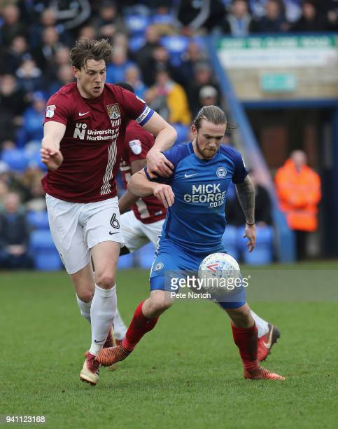 Jack Marriott of Peterborough United controls the ball under pressure from Ash Taylor of Northampton Town during the Sky Bet League One match between...