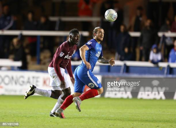 Jack Marriott of Peterborough United looks to the ball watched by Aaron Pierre of Northampton Town during the Checkatrade Trophy match between...