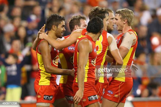 Jack Martin of the Suns celebrates a goal with team mates during the round 14 AFL match between the Gold Coast Suns and the Geelong Cats at Metricon...